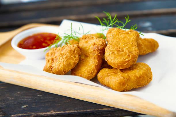 Hähnchen-Nuggets im Tablett aus Holz. – Foto