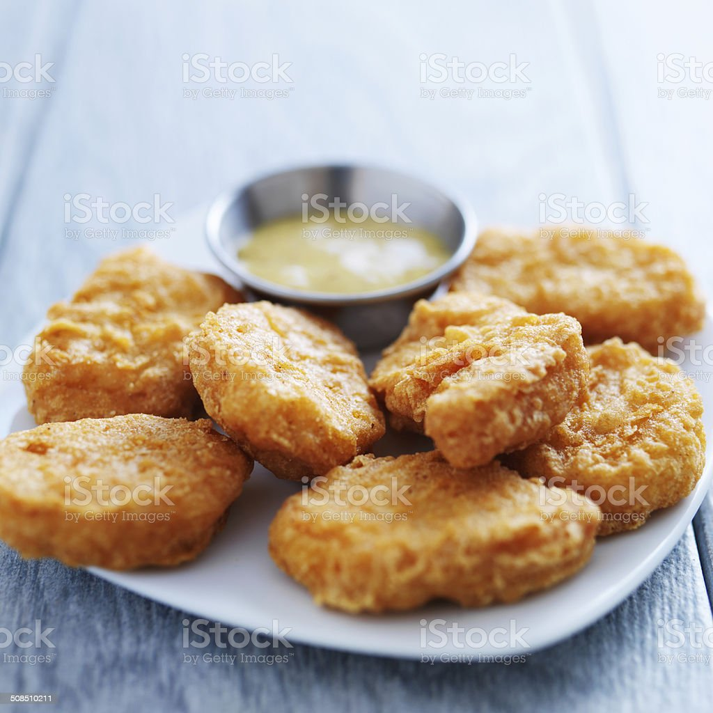 chicken nuggets with honey mustard in natural light stock photo