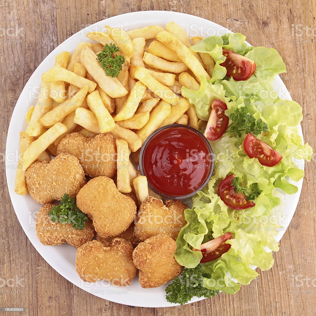 chicken nuggets,french fries and salad stock photo