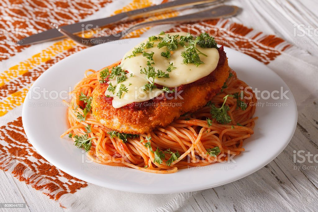 Chicken Parmigiana and pasta with tomatoes close-up
