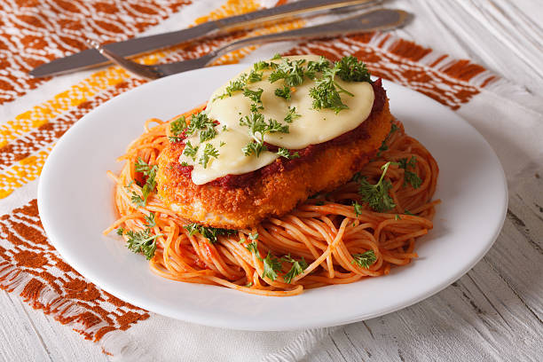 Chicken Parmigiana and pasta with tomatoes close-up stock photo