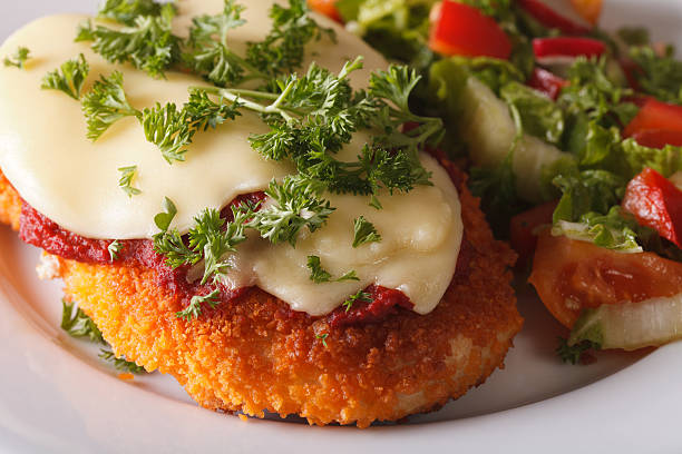 Chicken Parmigiana and vegetable salad macro. Horizontal Chicken Parmigiana and vegetable salad macro on a plate. Horizontal parmesan cheese stock pictures, royalty-free photos & images