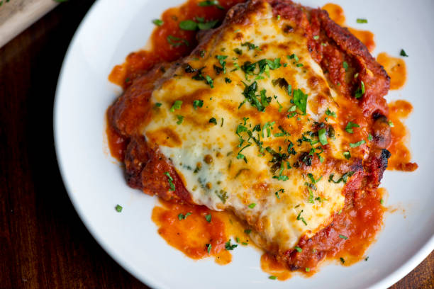 Chicken parmigiana Traditional Italian comfort dish. Chicken breast covered in breadcrumbs lightly fried, topped with homemade marinara, melted mozzarella, parmigiana provolone and Italian parsley. Chicken parmigiana Traditional Italian comfort dish. Chicken breast covered in breadcrumbs lightly fried, topped with homemade marinara, melted mozzarella, parmigiana provolone and Italian parsley. parmesan cheese stock pictures, royalty-free photos & images