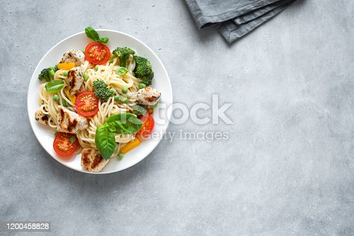 Chicken Pasta Spaghetti Primavera, homemade pasta dish with grilled chicken, vegetables tomato, broccoli, green pea, bell pepper and basil leaves, top view, copy space.