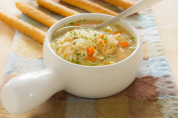 chicken rice soup with bread stick - chicken rice stock photos and pictures