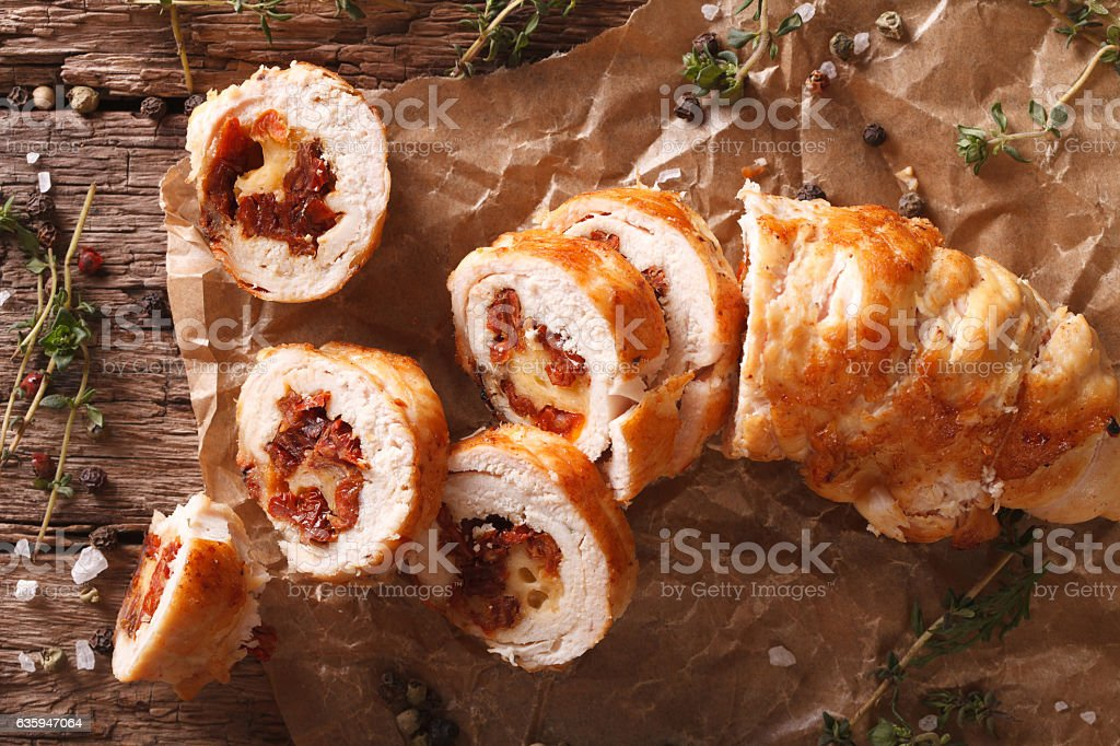 Chicken roll with cheese and sundried tomatoes close-up. Horizon stock photo