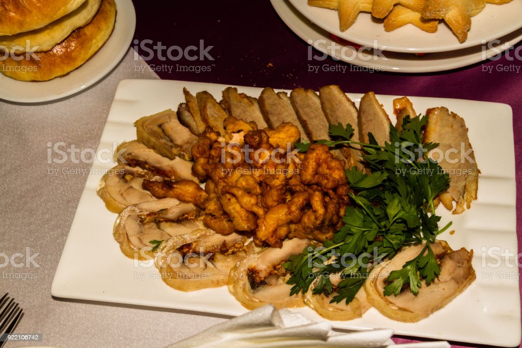 Chicken roule with dried apricots and fried meat. Foods laid out in restaurant for banquet. Almaty, Kazakhstan, Central Asia stock photo