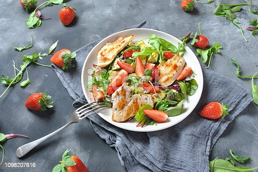 Chicken salad with avocado, strawberries,blue cheese, arugula, beet leaves. Healthy lunch avocado bowl, plate with chicken and strawberries on the dark gray background. Healthy food concept