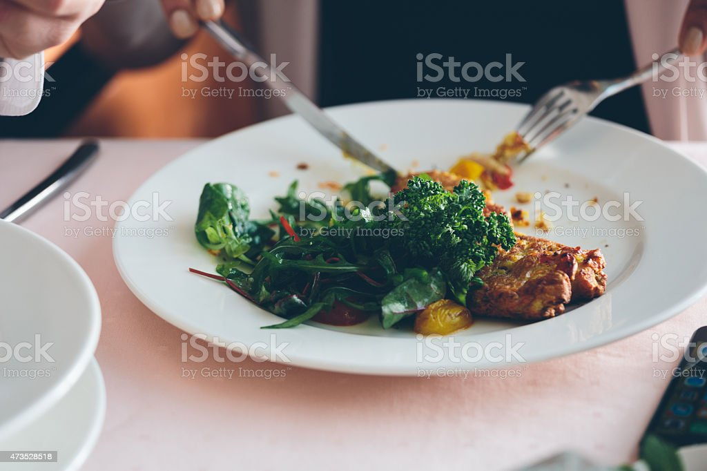 Chicken salat Woman eating salat in restaurant. Close up of hands, chicken salat and cutlery on the table. Unrecognizable person. 2015 Stock Photo