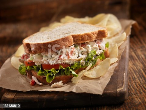 A Creamy Chicken Salad Sandwich with Red Peppers, Cucumber, Lettuce and Tomato on Whole Wheat Bread and Potato Chips on the side- Photographed on Hasselblad H3D2-39mb Camera