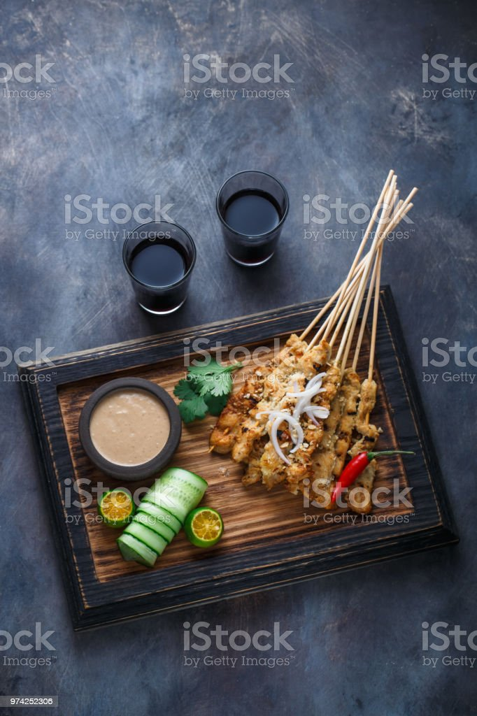Chicken Satay or Sate Ayam - Malaysian famous food. Is a dish of seasoned, skewered and grilled meat, served with a peanut sauce. Top view copyspace stock photo