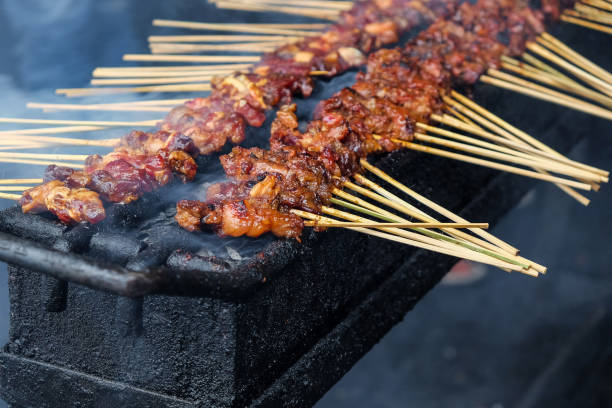 Chicken satay skewer on bbq coal grill stock photo