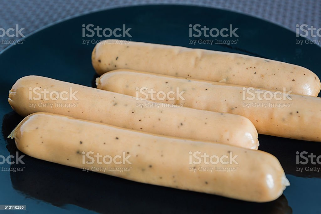 chicken sausages with black peppers on black dish stock photo