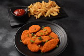 istock Chicken schnitzel or nuggets with chips and ketchup 1248418467