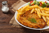 Chicken schnitzel, served with fries and salad. Natural wooden background. Front view.