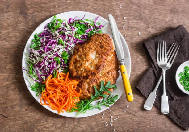 hähnchen schnitzel tempura, rotkohl, krautsalat und würzig eingelegte karotten auf einem hölzernen hintergrund, ansicht von oben. leckeres mittagessen - kürbisschnitzel stock-fotos und bilder