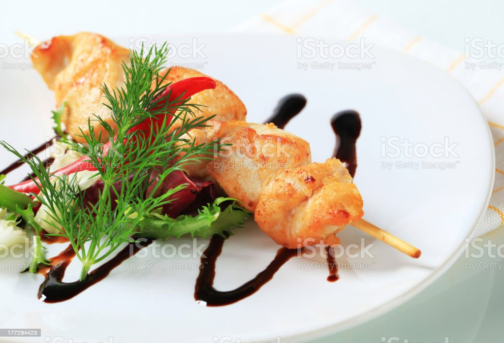 Chicken skewer garnished with salad green royalty-free stock photo