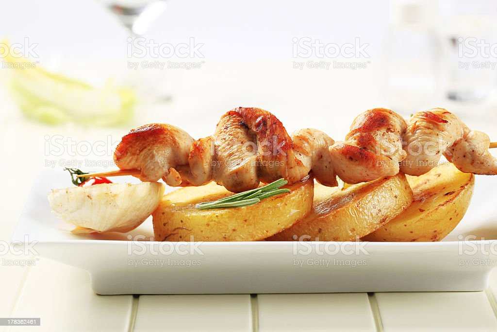 Chicken skewer on roasted potatoes royalty-free stock photo
