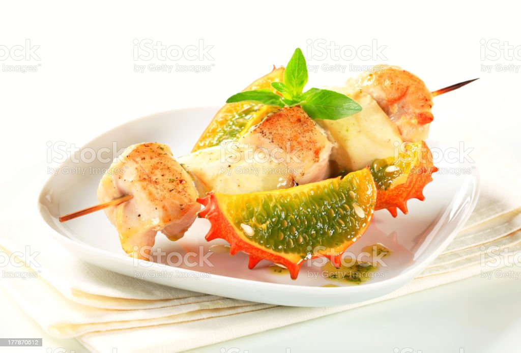 Chicken skewer with aubergine and horned melon stock photo