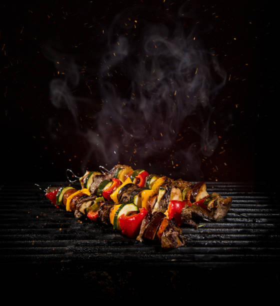 Chicken skewers on the grill with flames stock photo