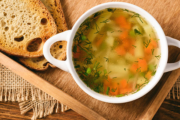 Chicken soup in white bowl on wooden tray. stock photo