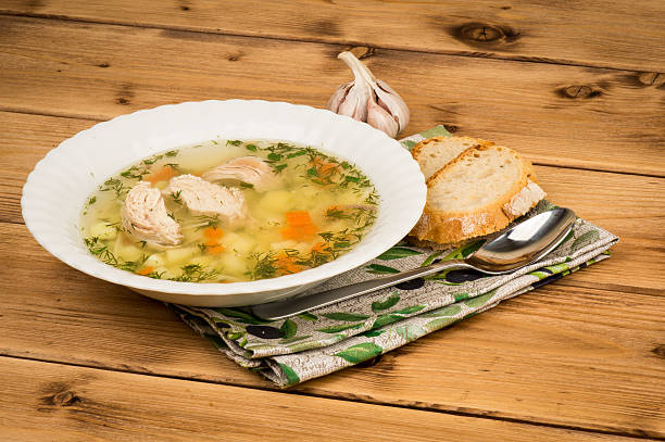 Chicken soup with  bread and garlic on the wooden background. stock photo