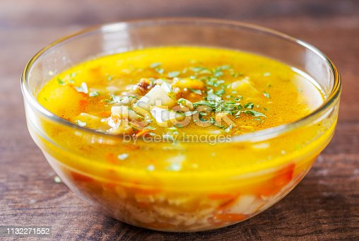 chicken soup with vegetables and rice in glass Bowl on wooden table background