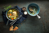 Eating Healthy Chicken soup with vegetables and herbs on dark background