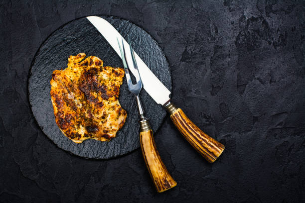 Chicken steak on slate board Chicken steak, fork and knife on slate board. Dark stone background. Copy space carving knife stock pictures, royalty-free photos & images
