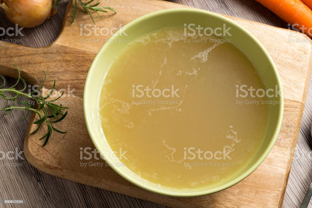 Chicken stock in a green soup bowl, top view stock photo