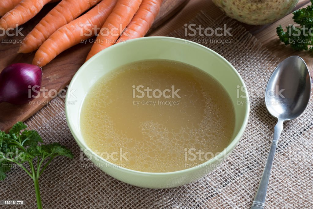 Chicken stock in a green soup bowl, with vegetables in the background stock photo