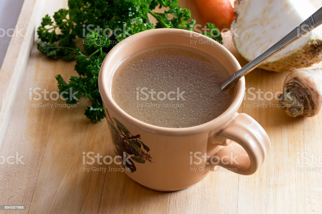 Chicken stock in a vintage mug with a spoon, with vegetables in the background stock photo