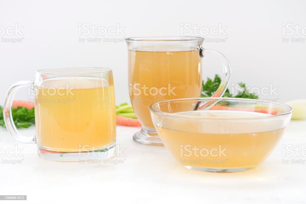 Chicken Stock in Glass Mugs and Bowl stock photo