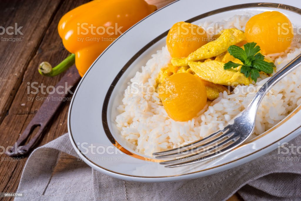 Chicken strips with rice and sweet mirabelle in curry sauce royalty-free stock photo