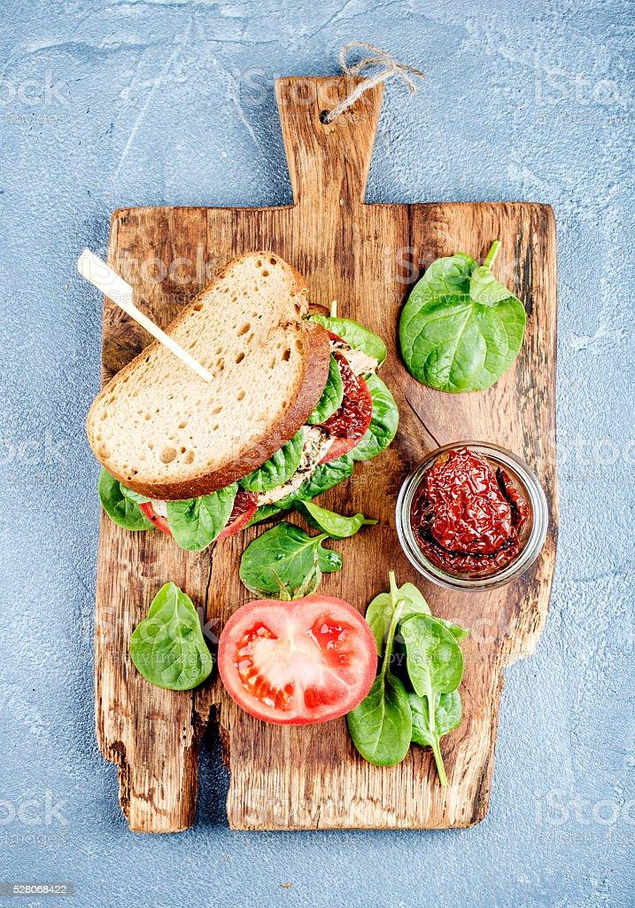 Hühnchen, getrocknete Tomaten und Spinat-sandwich mit pikanter soße – Foto