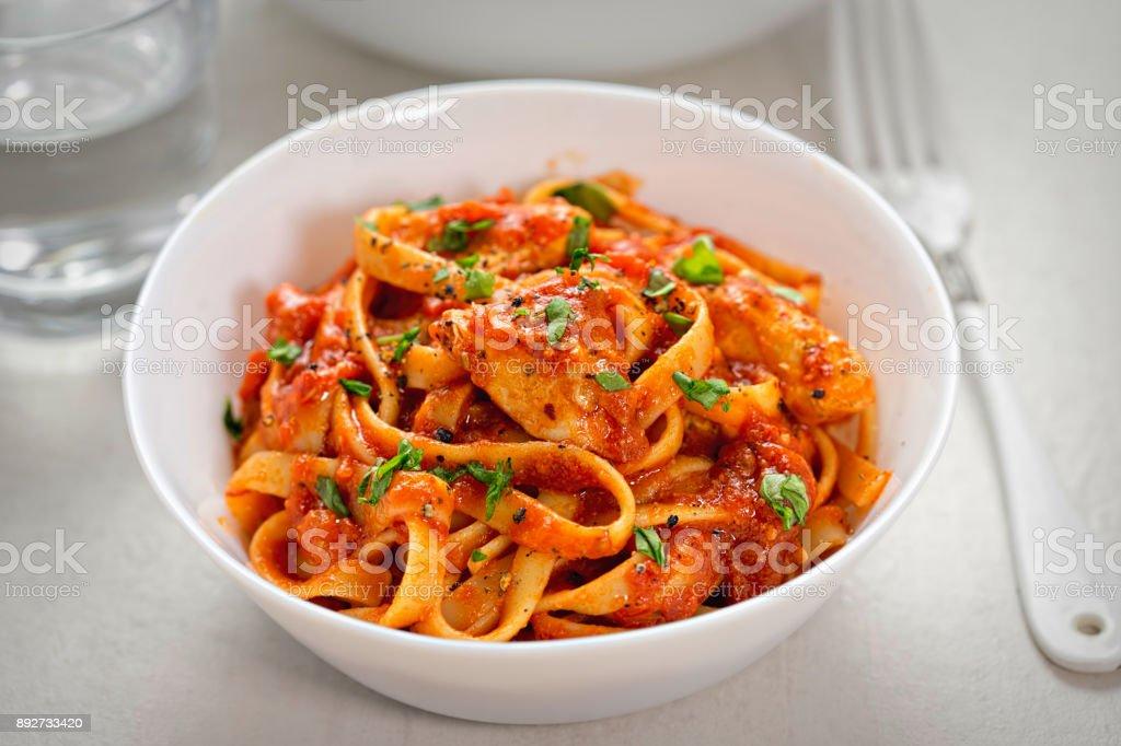 Chicken tagliatelle in tomato sauce stock photo