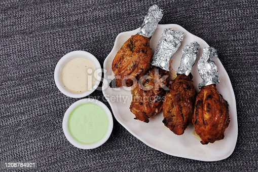 Chicken tandoori legs made with pungent marinade of spices and yogurt and cooked in a tandoor or oven