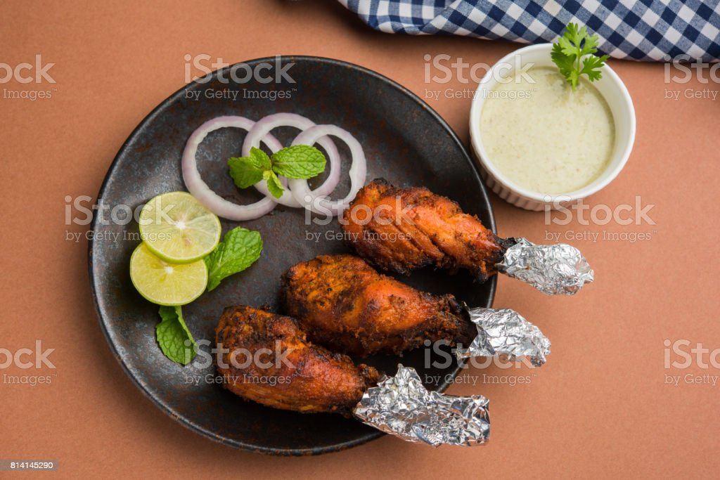 Chicken Tangri kabab or kebab - three Chicken leg pieces marinated with red sauce then grilled and served with salad. It can be served with green chutney stock photo