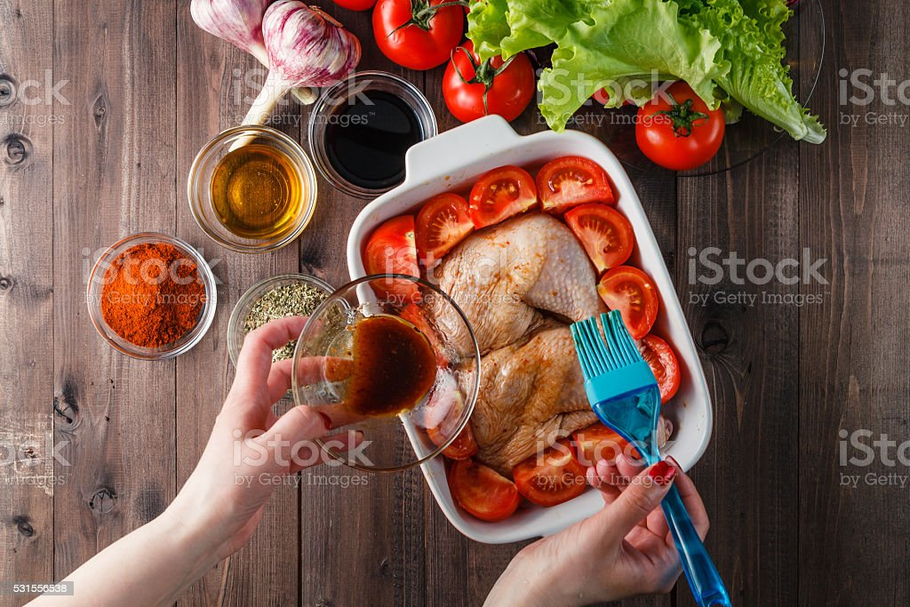 Chicken thighs marinated in spices on a baking sheet stock photo