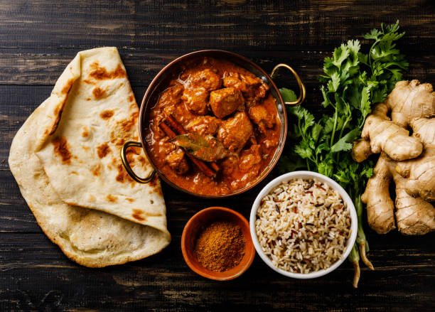 Chicken tikka masala spicy curry meat food with rice and naan bread stock photo