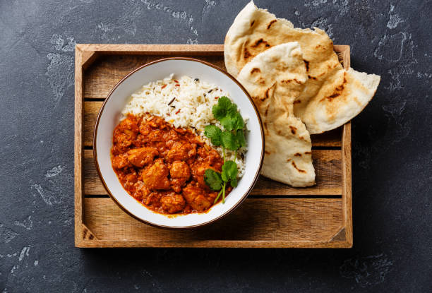 Chicken tikka masala spicy curry meat food with rice Chicken tikka masala spicy curry meat food with rice and fresh naan bread in wooden tray on black stone background naan bread stock pictures, royalty-free photos & images