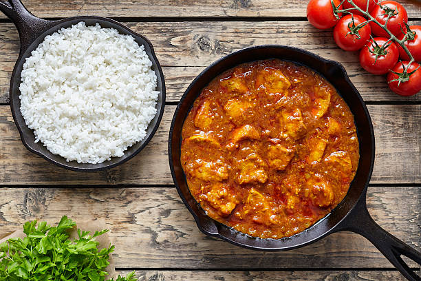 Chicken tikka masala traditional Asian spicy meat food with rice Chicken tikka masala traditional Asian spicy meat food with rice tomatoes and parsley in cast iron pan on vintage wooden background balti dish stock pictures, royalty-free photos & images