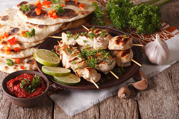 chicken tikka on skewers, flat bread and chutney closeup. horizontal - kebab marinade stock-fotos und bilder