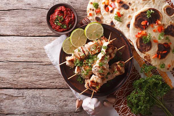 chicken tikka on skewers, flat bread and chutney. horizontal - kebab marinade stock-fotos und bilder