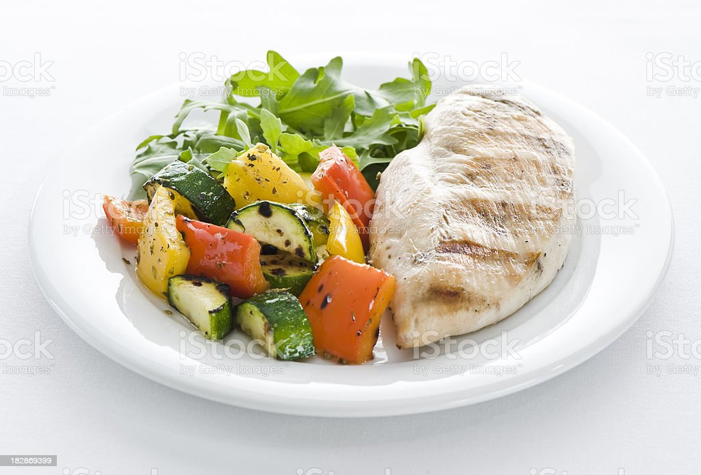 Chicken, vegetables and arugula salad stock photo
