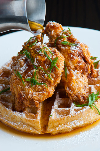 Waffles w/ fried chicken. Homemade Waffles w/ crispy chicken butter & maple syrup. Classic American breakfast or brunch favorite. Made from scratch Waffles  w/ chicken, butter & maple syrup.