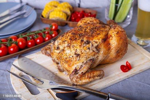 Курица целиком запеченная на соли. С кукурузой, томатами, огурцами и перцем халапеньо. Выборочный фокус, крупный план.