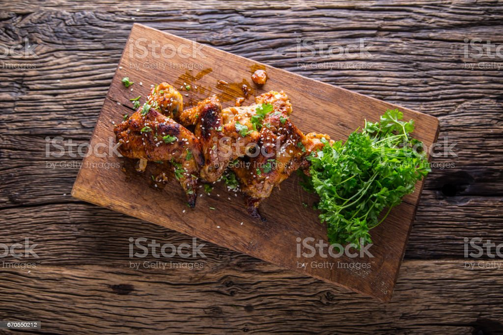 Chicken wings grilled BBQ  parsley herb and sesame on wooden board stock photo