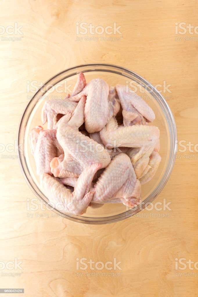 Chicken wings in a glass bowl. A glass dish with raw wings on a wooden table. stock photo