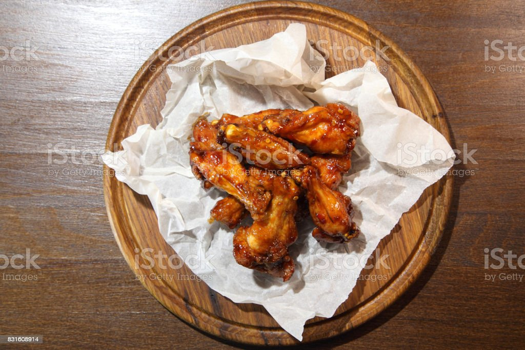 Chicken wings in hot sauce, specially prepared for beer. Chicken wings in hot sauce on a wooden plate. stock photo
